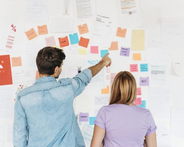 young-employees-looking-at-wall-with-marketing-notes